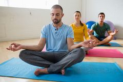Yoga instructor with students meditating at club. Yoga instructor with students meditating at health club Stock Photography