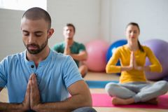 Yoga instructor with students meditating in prayer position at club. Yoga instructor with students meditating in prayer position at health club Stock Photography