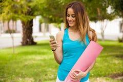 Yoga instructor texting Stock Image