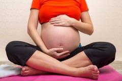 Yoga irriconoscibile di addestramento della donna incinta nella posa del loto, accarezzante la sua pancia fotografie stock