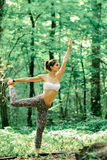 Yoga king of the dance pose by woman on green grass in the park Stock Photo