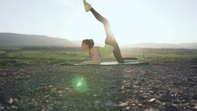 Yoga - la muchacha gimnástica hace el entrenamiento del ejercicio en el top de la montaña en fondo del río cerca de ejercicio de  metrajes