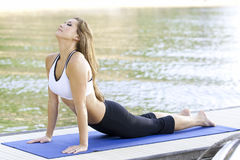 Yoga on the lake. Yoga performed on a dock by the lake Royalty Free Stock Photos
