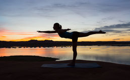 Yoga by the Lake at Sunrise. Silhouette of girl doing yoga at sunrise next to a lake during summer Royalty Free Stock Image