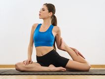 Yoga leg stretches. Photo of a thin attractive female in her early 20's doing yoga leg stretches Royalty Free Stock Photography