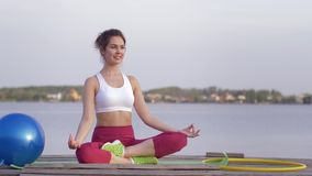 Yoga lifestyle, beautiful yogi woman in lotus position meditates and relish spiritual calmnes near water. Yoga lifestyle, beautiful yogi woman in lotus position stock video