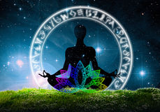 Yoga lotus position against night skies. Illustration of woman in lotus yoga position inside illustrated ring in green grass against starry night skies Royalty Free Stock Photos