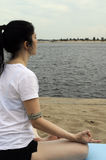 Yoga lotus river. Woman sitting in lotus position, looking at the river Royalty Free Stock Images