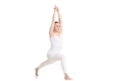 Yoga lunge exercise. Sporty beautiful young woman in white sportswear doing high lunge exercise, Warrior I posture, Virabhadrasana 1 with hands in Vajra arrow stock photos