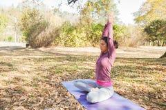 Yoga méditant et de pratique de jeune femme en bonne santé extérieur images libres de droits