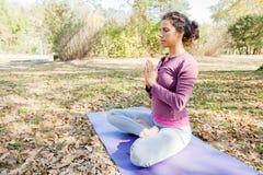 Yoga méditant et de pratique de jeune femme en bonne santé extérieur photos libres de droits