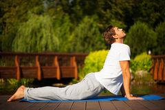 Yoga man in cobra pose. Young man practising yoga and standing in cobra pose with a beautiful green scenery of park on background Stock Images