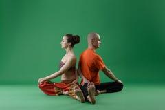 yoga Man- och kvinnasammanträdebaksidor till varandra Arkivfoton