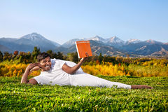 Yoga man reading the book. Indian Man in white cloth doing Yoga eka pada shirshasana foot behind the head pose and reading orange book at mountain and blue sky Stock Photography