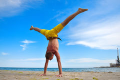 Yoga man standing on hands. And does the splits Royalty Free Stock Photo