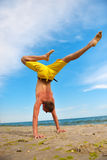 Yoga man standing on hands. And does the splits Royalty Free Stock Images