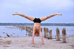 Yoga man standing on hands. And does the splits on pristine beach Stock Image