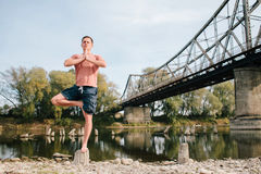 Yoga man standing near the river on the stump Stock Photography