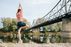 Yoga man standing near the river on the stump. Royalty Free Stock Photos