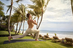 Yoga man at tropical beach Stock Photography