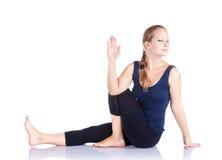 Yoga marichiasana twist pose. Beautiful Caucasian woman in blue Capri and top doing marichiasana III, twist pose at white background. Free space for text Stock Images