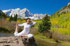 Yoga at Maroon Bells. A woman practicing yoga in the scenic maroon bells in fall as a backdrop Stock Images