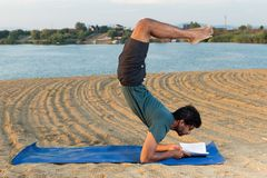 Yoga master reading in headstand royalty free stock photography