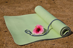 Yoga Mat. A yoga mat half rolled on sand with a hibiscus flower Stock Photos