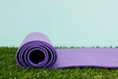 Yoga Mat. Purple Yoga Exercise Mat On Green Grass Stock Photos