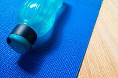 Yoga mat and a bottle of water royalty free stock images