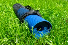 Yoga mat in a cover on green grass, the concept of training and recreation. stock photo