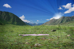 Yoga mat on green field near mountains Royalty Free Stock Photos