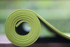 Yoga mat. A green yoga mat sets on the floor Stock Photos