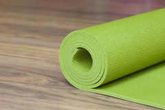 A yoga mat. A green yoga mat sets on the floor Stock Photos