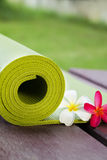 Yoga mat. A green yoga mat sets on the floor aside with flowers Royalty Free Stock Images