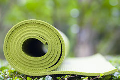 Yoga mat. A green yoga mat sets on grass Stock Image
