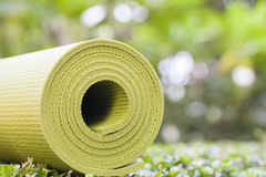 Yoga mat. A green yoga mat sets on grass Stock Photos