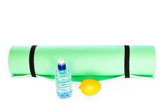 Yoga Mat roll with bottle of water and lemon on white background Stock Photos