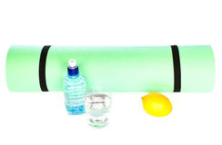 Yoga Mat roll with bottle of water on white background Royalty Free Stock Images