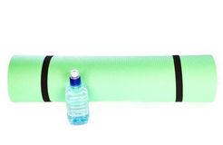 Yoga Mat roll with bottle of water on white background Stock Images