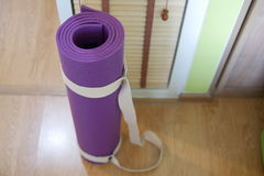 Yoga mat. Rolled purple yoga mat with strap on the wooden floor. Selective focus Stock Images
