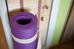 Yoga mat. Rolled purple yoga mat with strap on the wooden floor. Selective focus Royalty Free Stock Photography