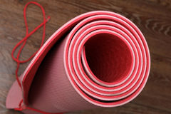 Yoga mat. Rolled red yoga mat on the wooden floor Royalty Free Stock Photos