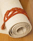 Yoga mat and rosaries Royalty Free Stock Images