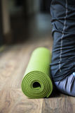 Yoga Mat. A yoga Mat is set on the floor next to a woman Stock Photo