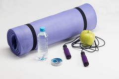 Yoga mat with skipping rope, water bottle, abs Royalty Free Stock Images