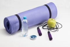 Yoga mat with skipping rope, water bottle, abs Stock Photo