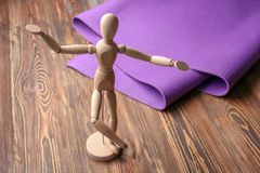 Yoga mat and small mannequin on wooden background royalty free stock photo