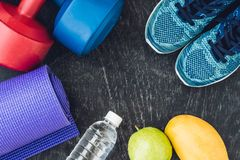 Yoga mat, sport shoes, dumbbells and bottle of water on blue background. Concept healthy lifestyle, sport and diet. Sport equipmen Royalty Free Stock Image