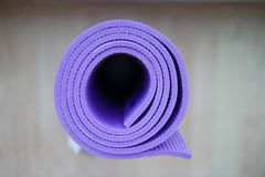 Yoga mat. Top view of rolled purple yoga mat with strap on the wooden floor. Selective focus Royalty Free Stock Photos
